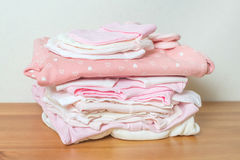Pile of clothes for newborn girl on wooden background with toy Royalty Free Stock Image