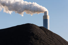 Pile of coal with the chimney of a coal power plant behind Stock Images
