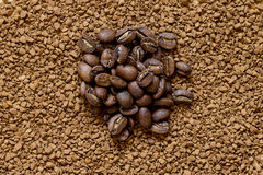Pile of cofee seeds on instant granulated cofe background Royalty Free Stock Photos