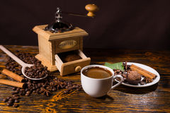 Pile of coffee beans besides open grinder Royalty Free Stock Image
