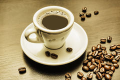 Pile of coffee beans and a cup. On a gray table Stock Images