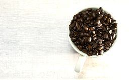 A pile of coffee beans in a cup royalty free stock photography