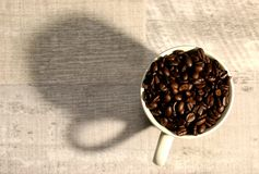 A pile of coffee beans in a cup royalty free stock photos