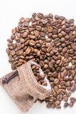 Pile of coffee beans and jute drawstring bag on the white background Stock Photo