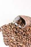 Pile of coffee beans and jute drawstring bag on the white background Royalty Free Stock Images