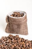Pile of coffee beans and jute drawstring bag on the white background Stock Photos