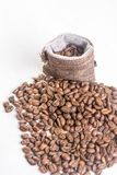 Pile of coffee beans and jute drawstring bag on the white background Royalty Free Stock Photos