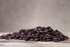 Pile of coffee beans on wooden table opposite a defocused burlap Royalty Free Stock Photography