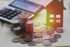 Pile of coin with calculator and  house Stock Images