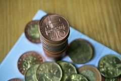 Pile of coins with a brass Czech Crown coin in the monetary value of 10 CZK on the top. Pile of coins on the wooden table with a brass Czech Crown coin in the Stock Photography