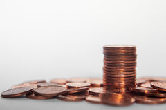 Pile of coins and a coin stack between it white background. Pile of coins and a coin stack between Royalty Free Stock Photo
