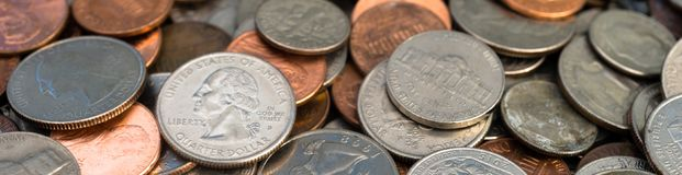Pile of American Dollar Currency Coins Quarters Dimes Nickels Pennies. A pile of coins is cropped into a long horizontal panoramic composition stock image