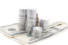 Pile of coins on dollar banknotes Stock Photos