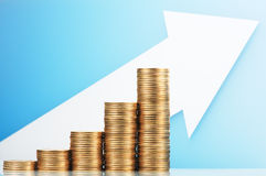 Pile of coins and growing arrow. Earning and saving more money. Royalty Free Stock Image