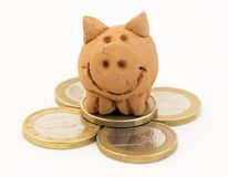 Pile of coins with small piggy toy Stock Photo