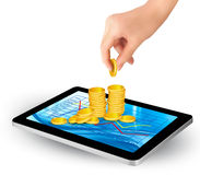 Pile of coins on a tablet. Internet job concept. Royalty Free Stock Photo