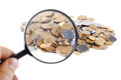 Pile of coins trough magnifying glass isolated on white backgrou Stock Photo