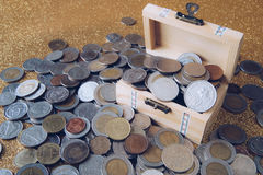 Pile of Coins from various countries in small wooden. Chest on golden glittering background Stock Image