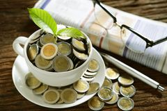 Pile of coins and young plant on top in coffee cup with newspapers Stock Image