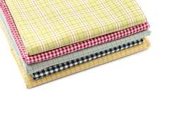 Pile of colored fabrics. Isolated on white background Stock Photos