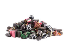 Pile of colored hard candy. A bunch of assorted liquorice hard candies on an all white surface Stock Photos