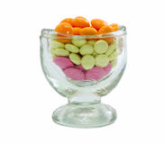 Pile of colored pills in glass. Heap of red and yellow tablets in glass on white Royalty Free Stock Image
