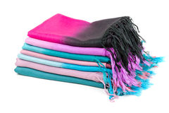 Pile of colored scarves with fringes. Pile of colored scarves stacked on a white background Stock Image