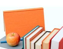 A pile of colorful books and apple Stock Photos