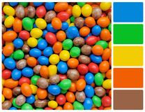 Pile of colorful chocolate coated candy with palette color swatc Royalty Free Stock Images