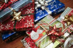 Colorful Pile of Christmas Presents. Pile of colorful Christmas presents with ribbons and bows on a wooden table. There is a blank tag on one of the gifts royalty free stock photos