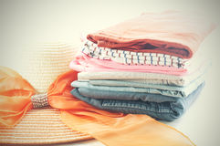 Pile of colorful clothes and Beautiful summer hat over white bac Stock Photos