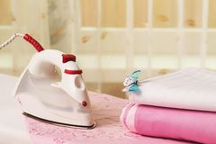 Pile of colorful clothes and electric iron Stock Images