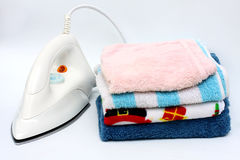 Pile of colorful clothes and electric iron Royalty Free Stock Image