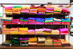 Pile of colorful fabrics on shelves Royalty Free Stock Photos
