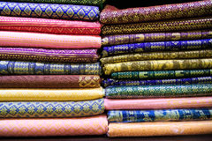Pile of colorful fabrics on shelves Royalty Free Stock Photo