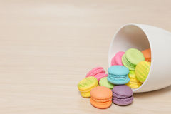 Pile of colorful macaroons cookies in cup on wooden with copy sp Stock Images