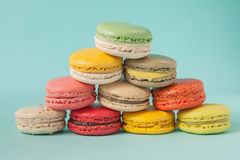 Pile of colorful macaroons stacked up like a tower in blue turquoise pastel  background. Royalty Free Stock Photo