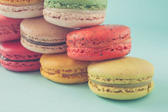 Pile of colorful macaroons stacked up like a tower in turquose pastel  background (Selective focus) - Closeup. Stock Image