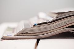 Pile of colorful magazines on a table. Pile of colorful magazines on a white table Royalty Free Stock Photos