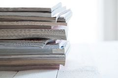 Pile of colorful magazines on a table. Pile of colorful magazines on a white table Royalty Free Stock Photo