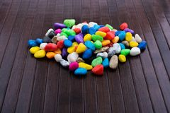 Pile of colorful pebbles on wooden background Stock Photos