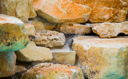 Pile of colorful rocks in Texas. Orange, green and brown mostly limestone rocks and slabs on a farm in Texas Stock Image