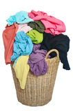 Pile of colorful shirts in a wicker basket, isolated white backg Stock Photo
