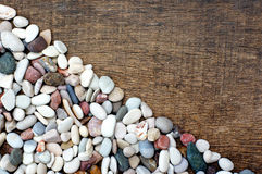 Pile of colorful stones on the wood texture. Pile of colorful stones diagonal position on the wood texture background Royalty Free Stock Photo