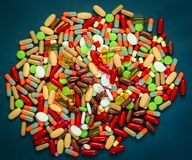 Pile of colorful tablets and capsules pills on blue background. Antibiotic resistance and drug use with reasonable concept. Pharmaceutical industry. Global Royalty Free Stock Images