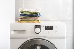 Pile of colorful towels lay in the laundry on washing machine and table b royalty free stock photography