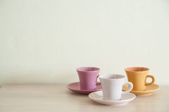 Pile of colorful vintage cups of coffee on wooden table Royalty Free Stock Photography