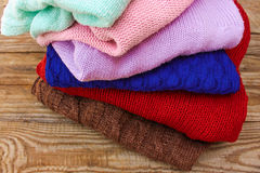 Pile of colorful warm clothes. On wooden background Royalty Free Stock Photo
