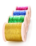 Pile of coloured bobbins of lurex thread isolated Royalty Free Stock Photos