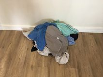 Pile of colourful laundry on laminate floor royalty free stock photography